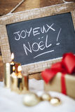 Christmas gifts with candles and slate. Royalty Free Stock Photography