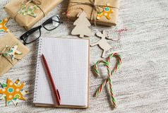 Christmas gifts, Christmas ornaments, candy and an open blank notebook Royalty Free Stock Photography