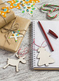 Christmas gifts, Christmas ornaments, candy and an open blank notebook Royalty Free Stock Images