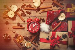 Christmas gifts, cinnamon, star anise and alarm clock Royalty Free Stock Photography