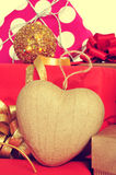 Christmas gifts. Closeup a heart-shaped ornament and some christmas gifts wrapped with wrapping paper of different colors and ribbon bows, with a retro effect royalty free stock images