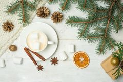 Christmas gifts, coffee with marshmallows, pine cones, spruce branches on a wooden white background. Flat lay. stock images