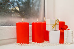 Christmas gifts in a composition with candles and beads. On a snow-covered window sill Royalty Free Stock Photos