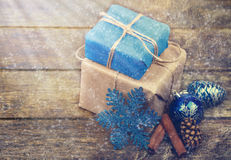 Christmas Gifts Decorated with Linen Cord, Cinnamon, Pine cones,Christmas Decoration . Toned image. Snow and Rays Drawn. Stock Images
