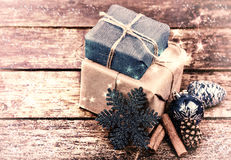 Christmas Gifts Decorated with Linen Cord, Cinnamon, Pine cones,christmas decoration . Vintage Toned image. Snow Drawn.Selective field of focus Royalty Free Stock Photo