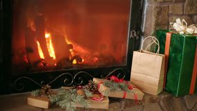 Christmas gifts decorated with spruce branches, cones, ribbons lay by the fireplace. Warm log fire burning. Christmas