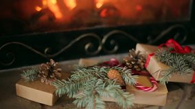 Christmas gifts decorated with spruce branches, cones, ribbons lay by the fireplace. Warm log fire burning. Christmas. Morning when Santa brought decorated stock footage