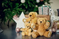 Cute little boy sitting down by the decorated Christmas tree with toys, teddy bears and gift boxes royalty free stock photo