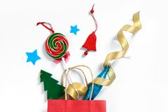Christmas gifts falling from the red shopping bag, holiday presents isolated on white background, holiday concept. Christmas gifts falling from the red shopping Stock Photography