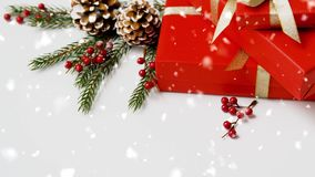 Christmas gifts and fir branches with pine cones. Winter holidays, christmas and celebration concept - snowing over red gift boxes and fir tree branches with stock footage