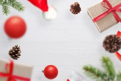 Christmas gifts, fir branches, Santa Claus`s hat and cones fall on a white wooden table stock image