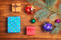 Christmas gifts, fir-tree branch and christmas toys. On wooden background Stock Photography