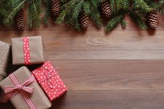 Christmas gifts and fit tree branches with cones on the wooden surface.  Royalty Free Stock Photo