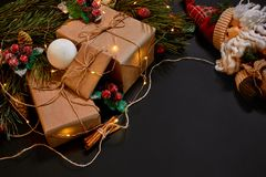 Christmas gifts and garland near green spruce branch on a black background. Christmas background. Top view. Stock Photos