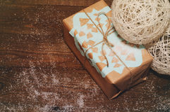 Christmas gifts. Christmas gift lies on a wooden table packed in kraft paper with a blue snowflake Stock Image