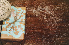 Christmas gifts. Christmas gift lies on a wooden table packed in kraft paper with a blue snowflake Royalty Free Stock Images