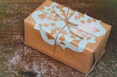 Christmas gifts. Christmas gift lies on a wooden table packed in kraft paper with a blue snowflake Royalty Free Stock Photo