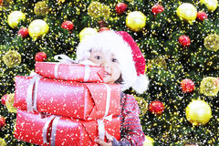 Christmas gifts from girl under pine tree Royalty Free Stock Image