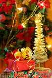 Christmas gifts and golden tree. Celebrating the magic of Christmas with golden lights tree and festive gifts royalty free stock photos