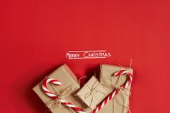 Christmas gifts on hot red background. Christmas and New Year theme. Place for your text, wishes, logo. Mock up.