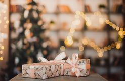 Christmas gifts in a Kraft package on the background of a garland. New year concept royalty free stock images