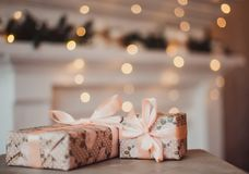 Christmas gifts in a Kraft package on the background of a garland. New year concept royalty free stock photo