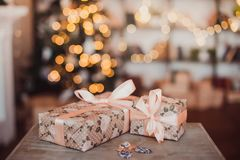 Christmas gifts in a Kraft package on the background of a garland. New year concept stock images