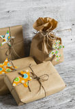 Christmas gifts in kraft paper on the bright wooden surface. Royalty Free Stock Images