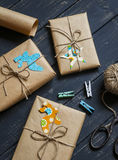 Christmas gifts in kraft paper on a dark wooden surface. vintage and rustic style. Stock Images
