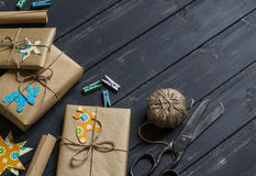 Christmas gifts in kraft paper on a dark wooden surface. vintage and rustic style. Stock Photos