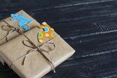 Christmas gifts in kraft paper with a homemade tag on a dark wooden surface. Royalty Free Stock Images