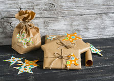 Christmas gifts in kraft paper with a homemade tag on a dark wooden surface. Royalty Free Stock Photography