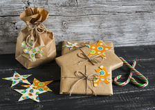 Christmas gifts in kraft paper with a homemade tag on a dark wooden surface. Stock Image