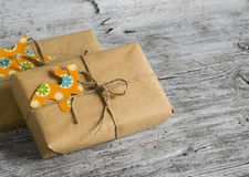 Christmas gifts in kraft paper with a homemade tag on a  wooden surface. Stock Photos