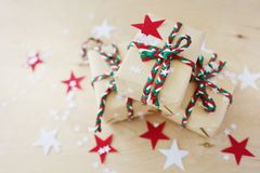 Christmas gifts in Kraft to packing on a wooden background stock images