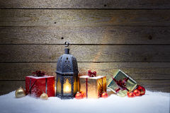 Christmas gifts with lantern in snow Royalty Free Stock Images