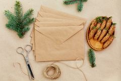 Christmas gifts and letters handmade, and everything necessary for them. Envelopes of Kraft paper, scissors, spruce cones and jute Stock Image