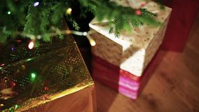 Christmas gifts in the light of garlands. Gifts under the Christmas tree stock video footage
