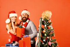 Christmas gifts and love concept. Santa and girl. With xmas gift boxes. Man with beard and women with happy faces on red background. Mister and Missis Claus royalty free stock images