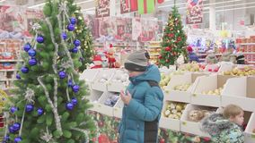 Christmas sale of toys and Christmas trees until Christmas. People in the supermarket are shopping before the new year. Christmas gifts for loved ones. Christmas stock video