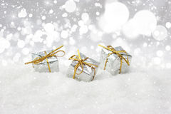Christmas gifts nestled in snow Stock Images