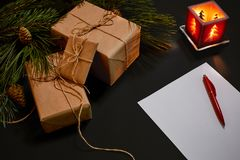 Christmas gifts and notebook lying near green spruce branch on black background top view. Space for text Stock Photos