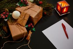 Christmas gifts and notebook lying near green spruce branch on black background top view. Space for text Royalty Free Stock Photography