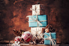 Christmas Gifts, Nuts, Fir Tree Toys on Wooden Background. Holiday Christmas Gifts with Boxes, Twine, Balls, Pine Cones, Walnuts, Fir Tree Toys on Wooden Royalty Free Stock Images