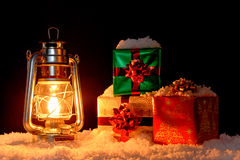 Christmas gifts and oil lamp on snow Royalty Free Stock Photography