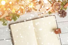 Christmas ornaments and an open blank notebook on a light wooden table. Christmas gifts, Christmas ornaments and an open blank notebook on a light wooden table Royalty Free Stock Image