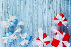 Christmas gifts packed with ribbons on wooden background stock photo