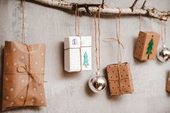 Free Christmas Gifts Packed With Kraft Paper And Hand Made Decorations Hang On A Rope Tied To A Stick Against A Gray Concrete Royalty Free Stock Photo - 164669395