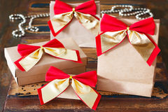 Christmas gifts paper package with red golden bow and chaplet Royalty Free Stock Images