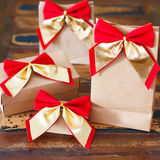 Christmas gifts paper package with red golden bow Stock Images